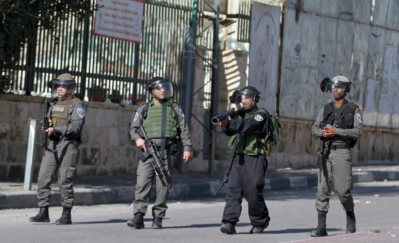 جنود إسرائيليون يوجهون أسلحتهم صوب محتجين فلسطينيين خلال اشتباكات في الضفة الغربية يوم 22 يناير كانون الثاني 2016. تصوير: عبد الرحمن يونس - رويترز