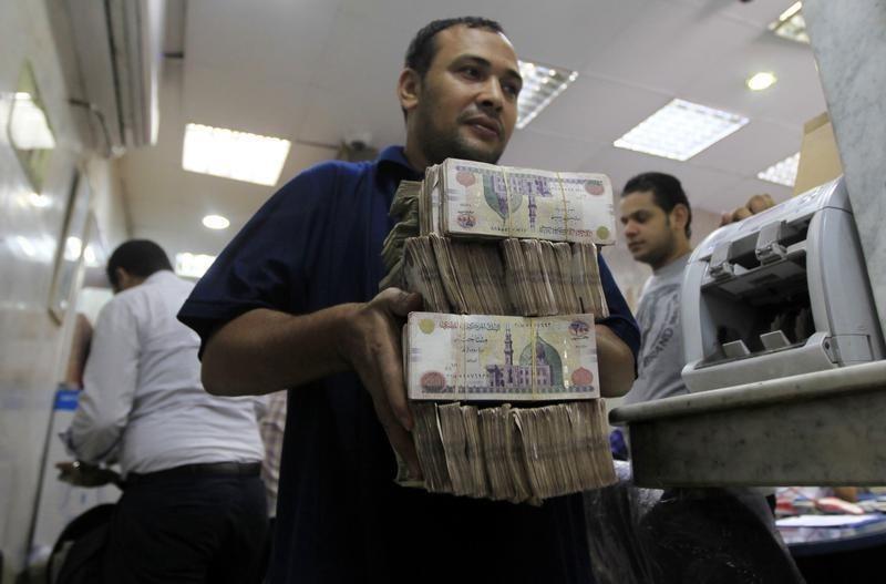 عامل بمحل صرافة بالقاهرة يحمل عملات مصرية، رويترز