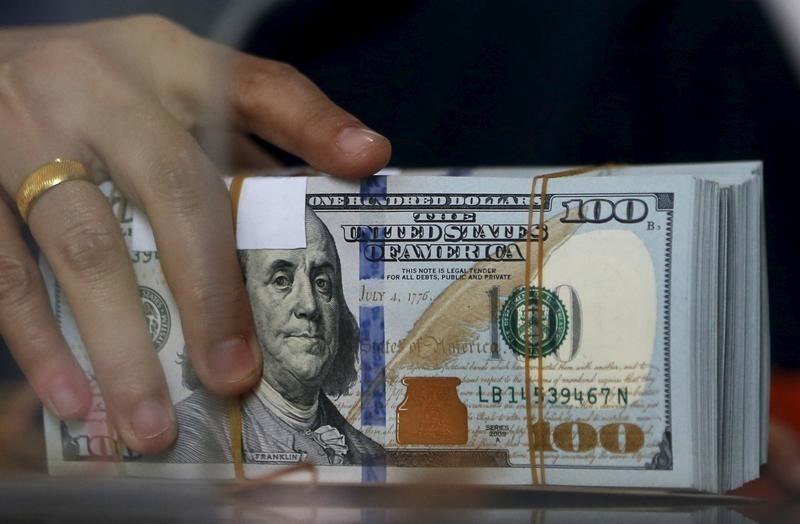 موظف في مكتب صرافة يحمل رزم أوراق مالية من الدولار الأمريكي في جاكرتا يوم 8 أكتوبر تشرين الأول 2015. تصوير: بياويهارتا - رويترز