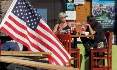 مواطنتان أمريكيتان في مطعم بجوار العلم الأمريكي - رويترز