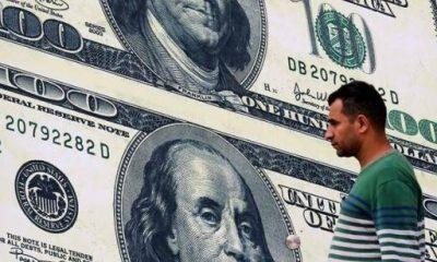 مواطن يسير أمام صرافة تعرض صورة الدولار الأمريكي. رويترز